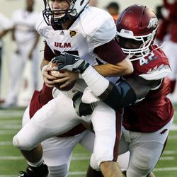 Louisiana Monroe quarterback Kolton Browning, left, is sacked by Arkansas defensive end Chris Smith (42) during the first quarter of an NCAA college football game in Little Rock, Ark., Saturday, Sept. 8, 2012.