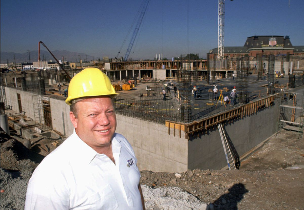 Larry H. Miller stand in front of early construction of the Delta Center in September of 1990.