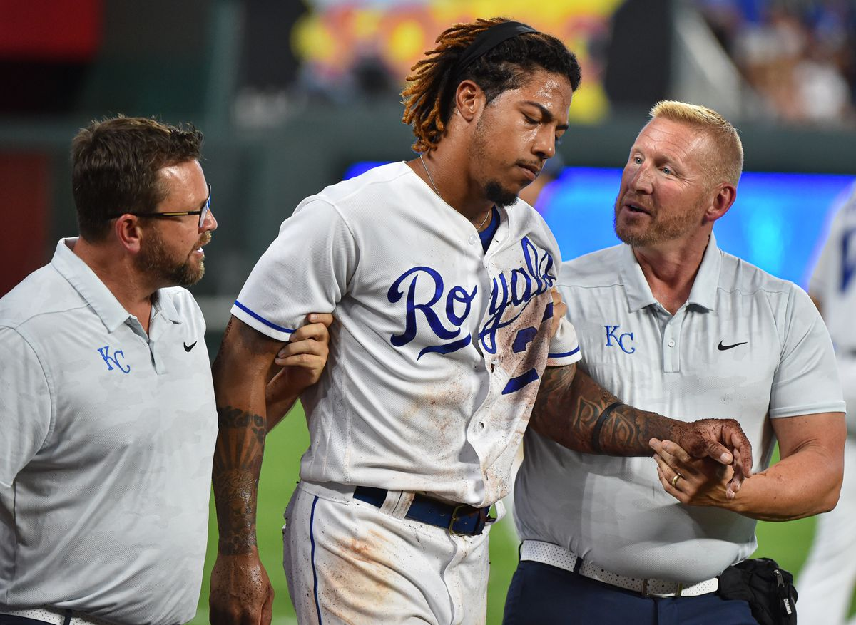 Adalberto Mondesi #27 of the Kansas City Royals is helped off the field by a team trainers after he was injured while trying to catch a foul ball hit by Yolmer Sanchez #5 of the Chicago White Sox in the fifth inning at Kauffman Stadium on July 16, 2019 in