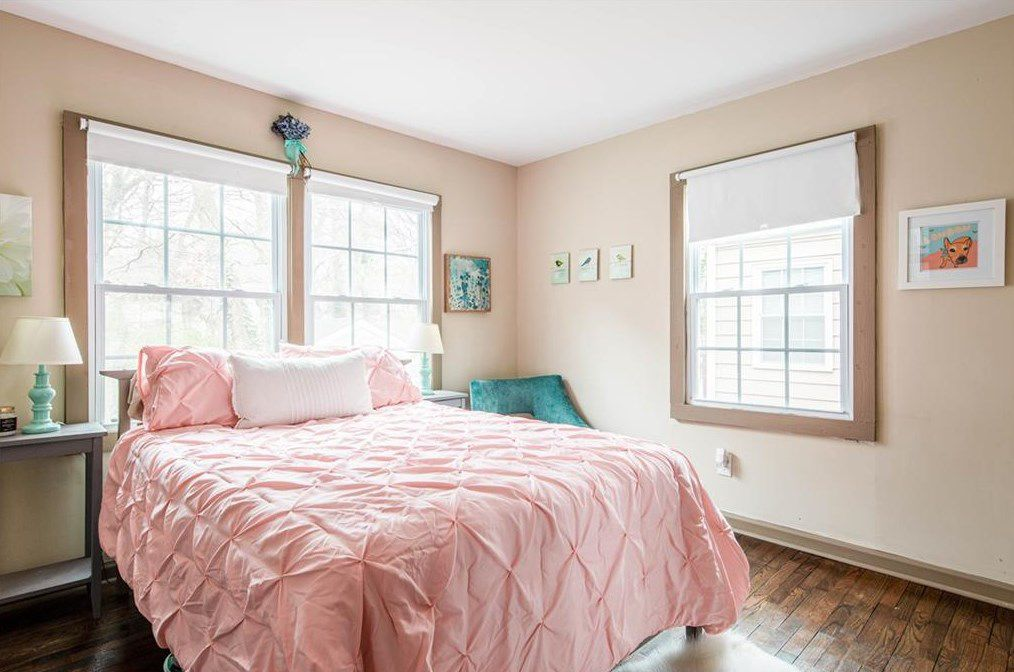 A beige room that's being used as a bedroom with a pink bedspread.
