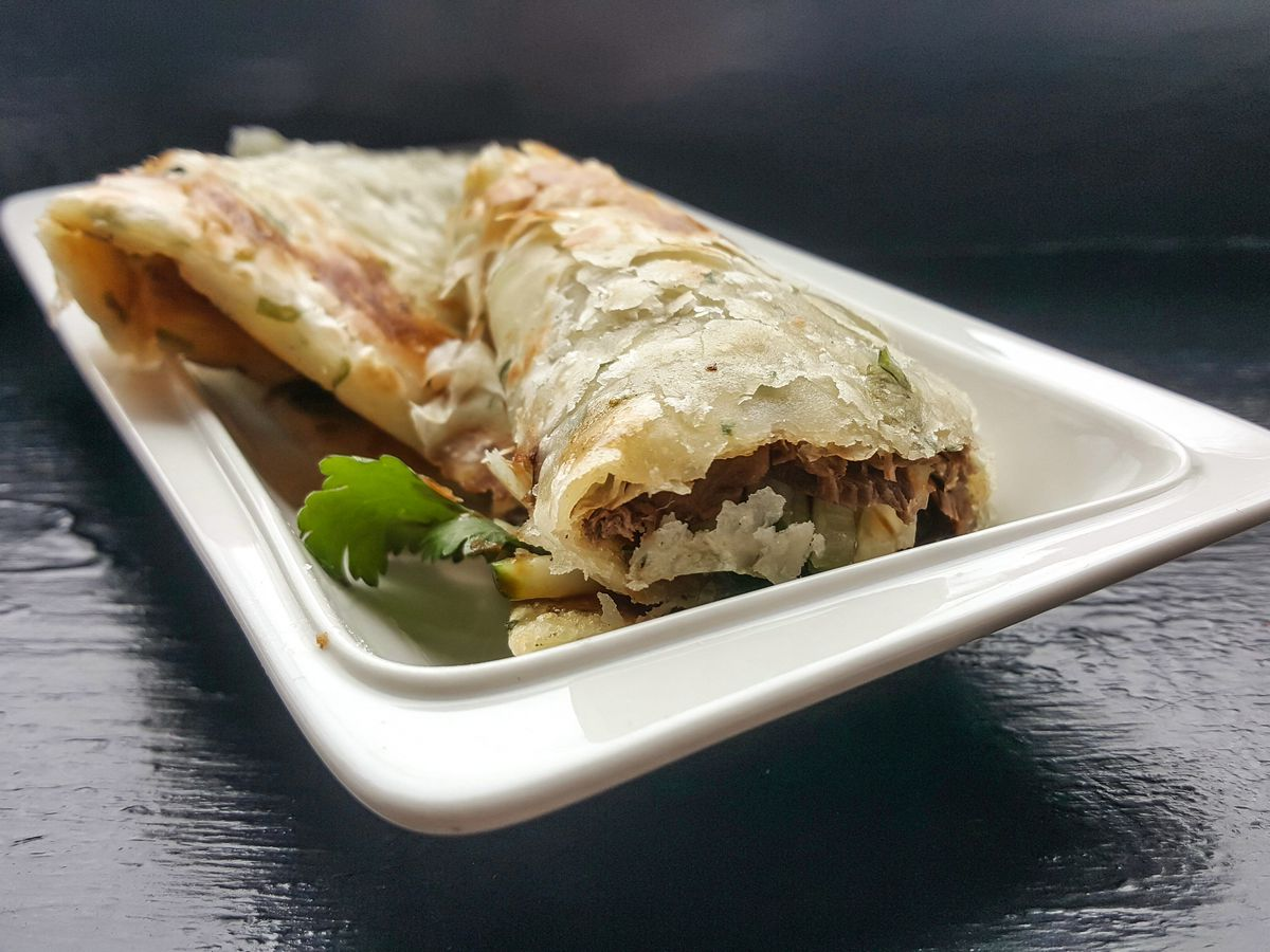 Beef is wrapped in a flaky scallion pancake, sitting on a white plate on a black tabletop