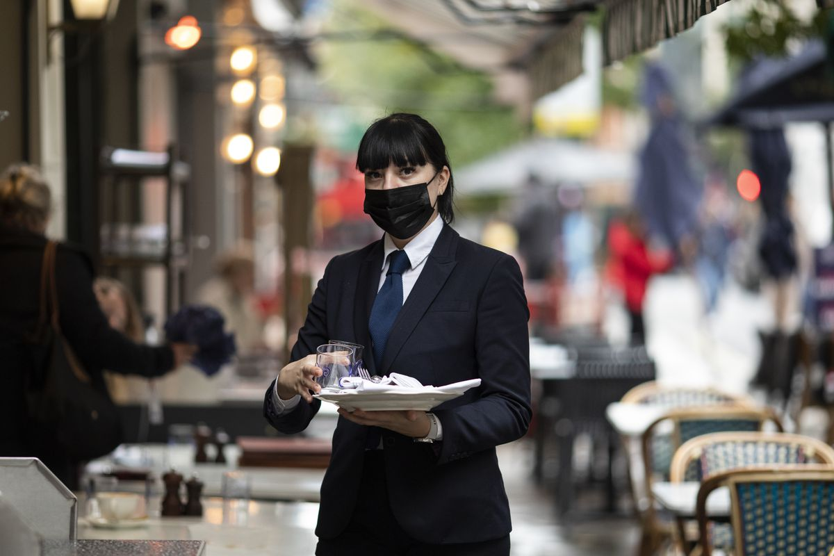 A waiter in a mask outside a London restaurant