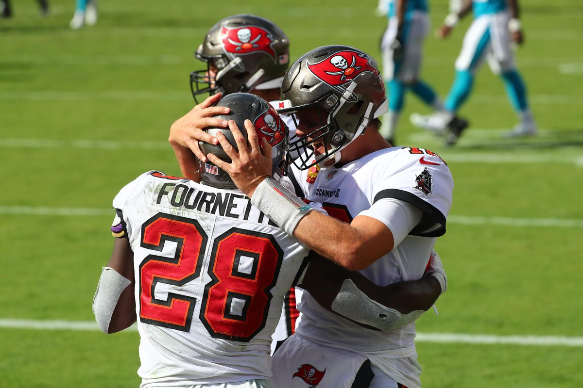 Tampa Bay Buccaneers running back Leonard Fournette celebrates with quarterback Tom Brady after scoring a touchdown against the Carolina Panthers during the fourth quarter at Raymond James Stadium