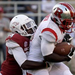 Rutgers running back Jawan Jamison, right, is tackled by Arkansas safety Eric Bennett (14) during the first quarter of an NCAA college football game in Fayetteville, Ark., Saturday, Sept. 22, 2012.