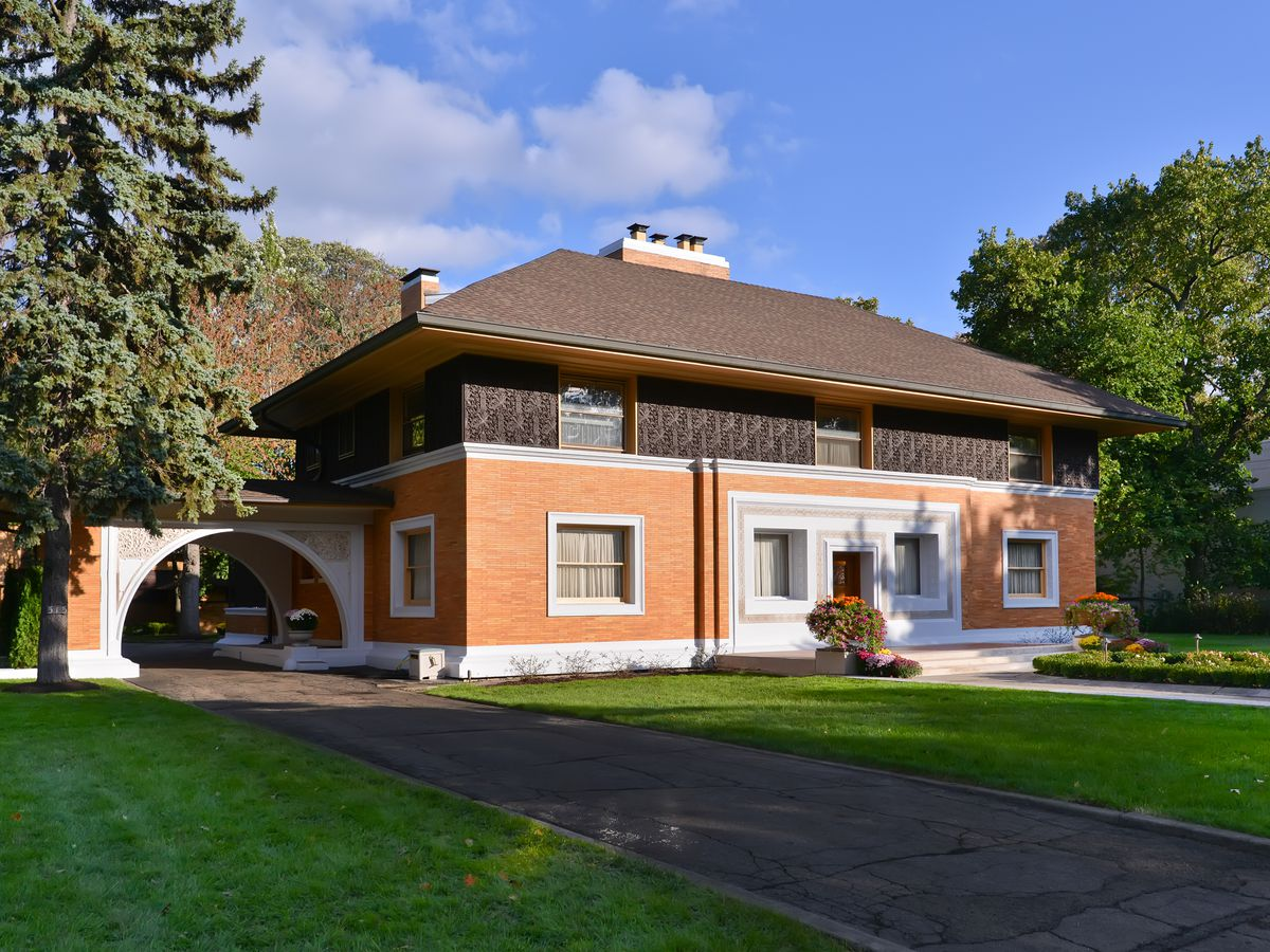The William H Winslow House by Frank Lloyd Wright. The house has a red brick exterior with a dark brown roof. There is a green lawn in front.