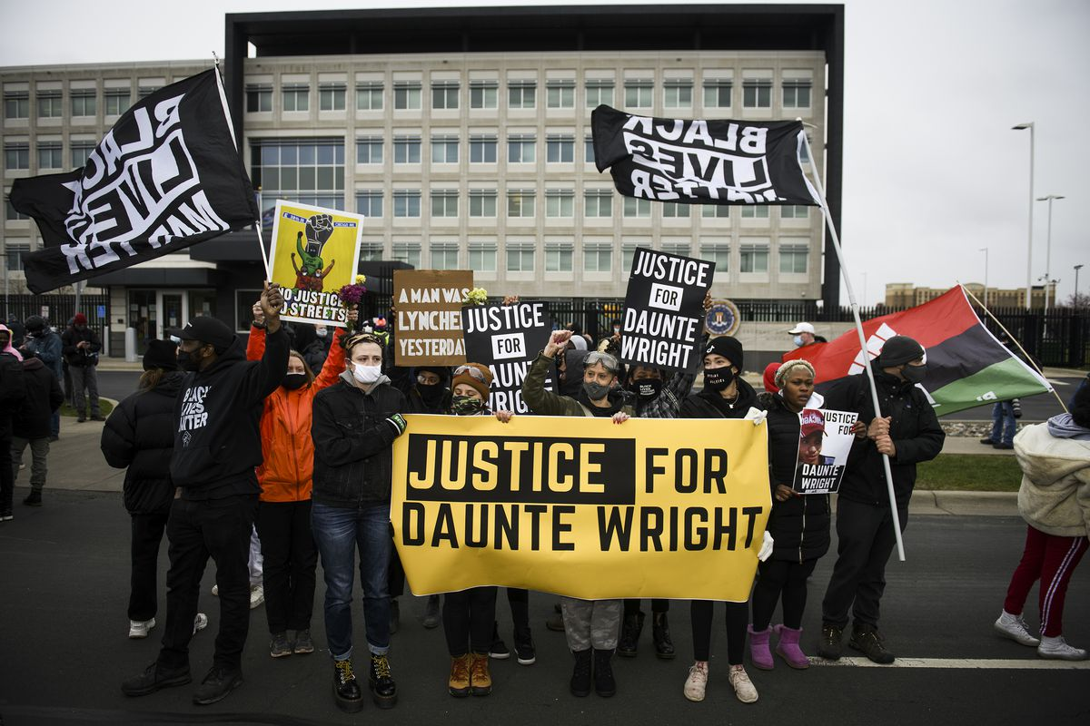 """Protesters march with a banner reading """"Justice for Daunte Wright"""" and """"Black Lives Matter"""" flags, in Brooklyn Center, Minnesota."""