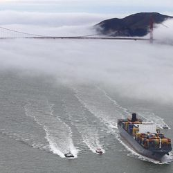 File - In this March 21, 2012 file photo, the San Francisco Bar Pilots boat Drake, second from left, and container ship MSC Fabiola enters San Francisco Bay enroute to the Port of Oakland on Wednesday, March 21, 2012, in San Francisco with the Golden Gate Bridge in the background.  Since the days of Mark Twain, the pilots have had it good. Thanks to political clout and highly specialized training, this cadre of 60 ship captains has for more than a century had control over guiding oil tankers and cargo ships in, out and around the San Francisco Bay.
