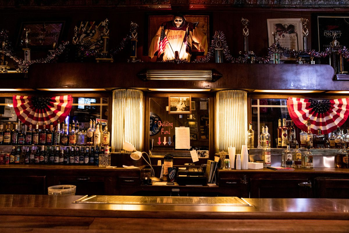 The interior of Carbon Athletic Club features an old school bar with lots of liquor bottles, mirrors, and American flag banners. There's also a grim reaper above the register.