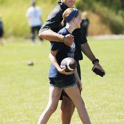 Utah State University football coach Matt Wells gives his daughter Jadyn a hug during a kids football camp in Logan Friday, June 12, 2015.