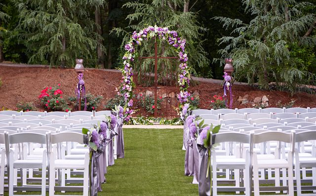 An outdoor wedding space. There is floral chapel in the front of the space. There are many rows of white chairs in front of the floral chapel.