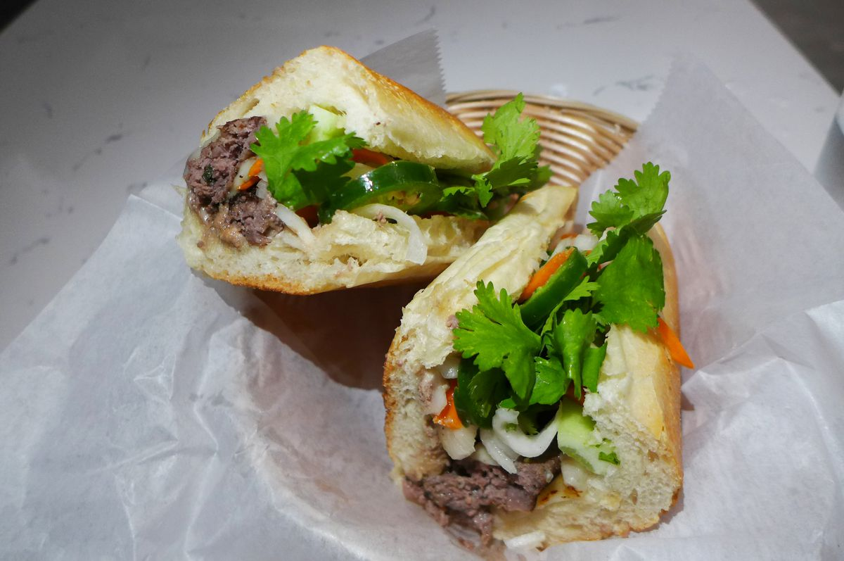 A pair of crossed half sandwiches with hamburger and pickled vegetables visible.