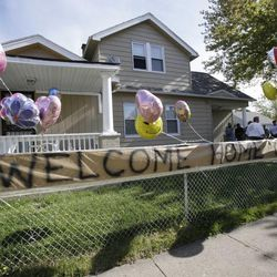 """A """"Welcome Home Gina """" sign hangs on a fence outside the home of Gina DeJesus  Tuesday, May 7, 2013, in Cleveland.  DeJesus, Amanda Berry and Michelle Knight, who went missing separately about a decade ago, were found in a home just south of downtown Cleveland and likely had been tied up during years of captivity, said police, who arrested three brothers."""