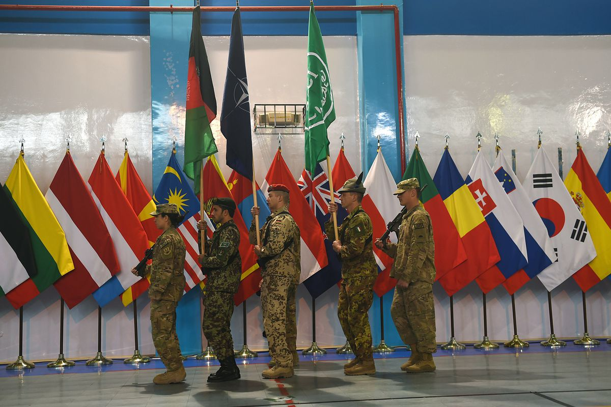 Soldiers carry flags at the secret ceremony officially ending the NATO-led war in Afghanistan