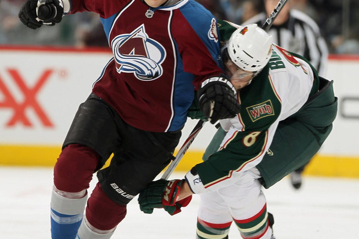 DENVER - DECEMBER 23:  Kevin Porter #12 of the Colorado Avalanche brushes off Brent Burns #8 of the Minnesota Wild as they vie for the puck at the Pepsi Center on December 23 2010 in Denver Colorado.  (Photo by Doug Pensinger/Getty Images)