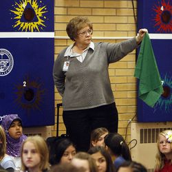 Cheryl Milano holds up a green cloth to show that all her students are accounted for as Vista Elementary participates in an earthquake drill in Taylorsville, Tuesday, April 17, 2012. This was part of The Great Utah ShakeOut.