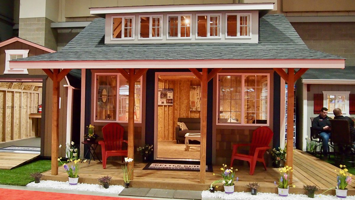 A backyard cottage with a small porch with two red chairs