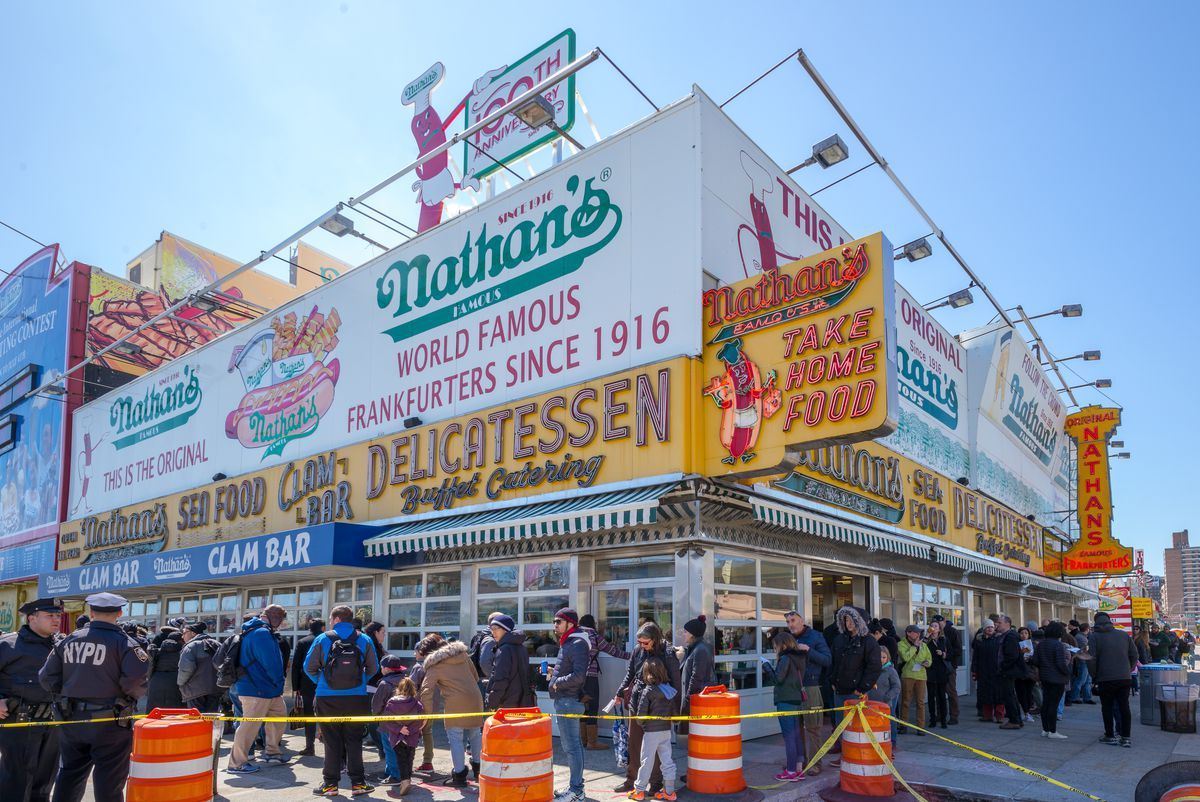 Customers wait in a line that wraps around the corner of the colorful Nathan's Famous restaurant in Coney Island