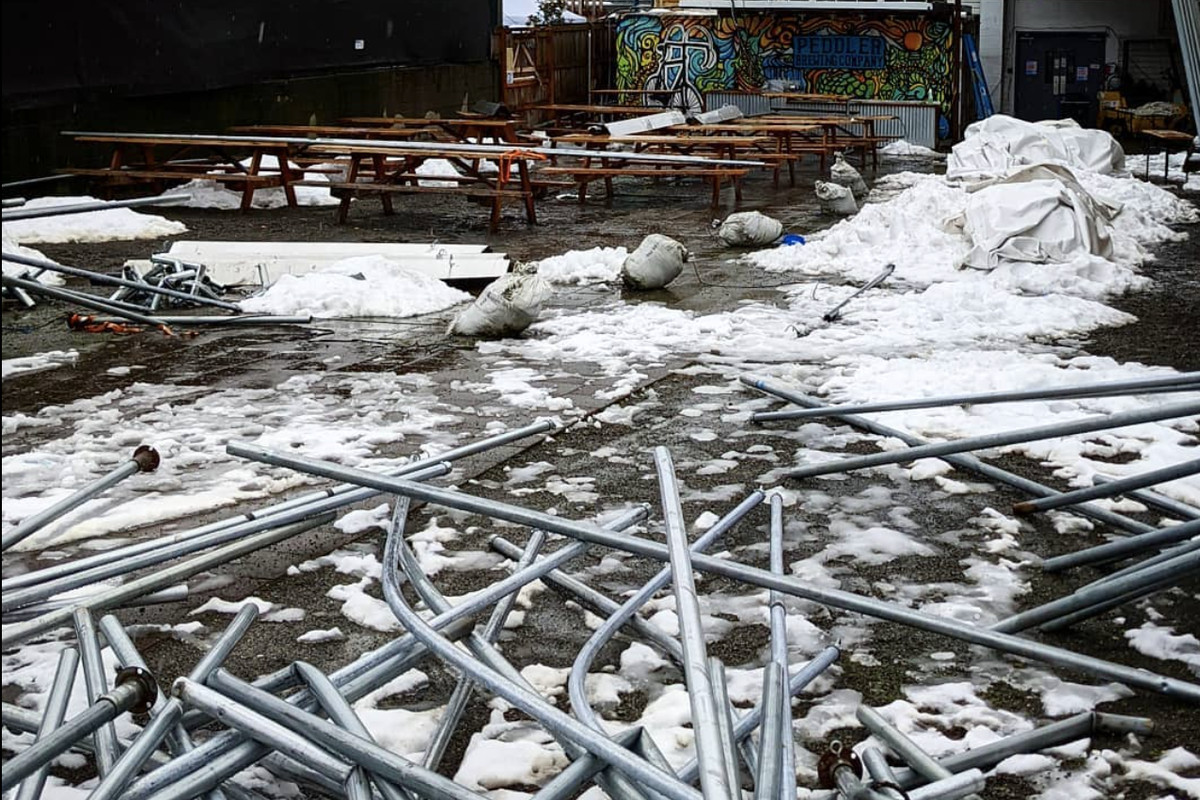 Metal rods from an outdoor tent lay scattered on the snowy ground in front of Peddler Brewing in Ballard.