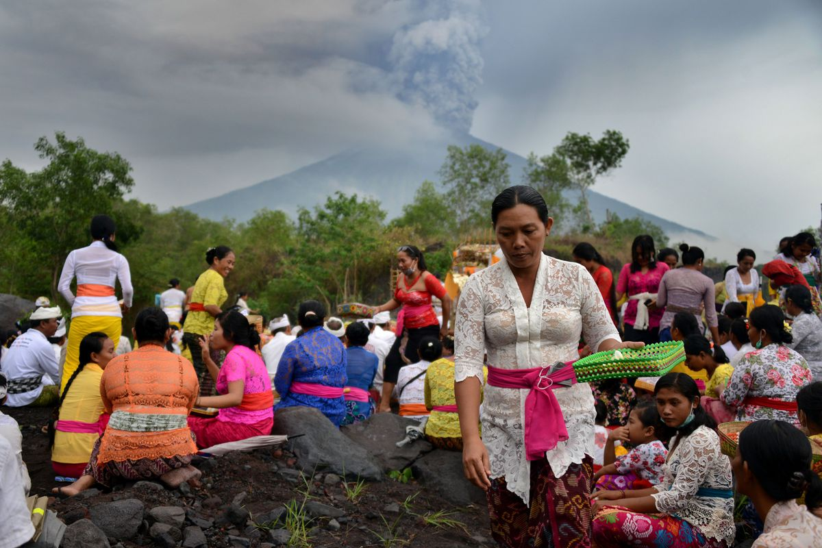 Balinese Hindus take part in a ceremony, where they pray near Mount Agung in hope of preventing a volcanic eruption, in Muntig village of the Kubu sub-district in Karangasem Regency on Indonesia's resort island of Bali on November 26, 2017.