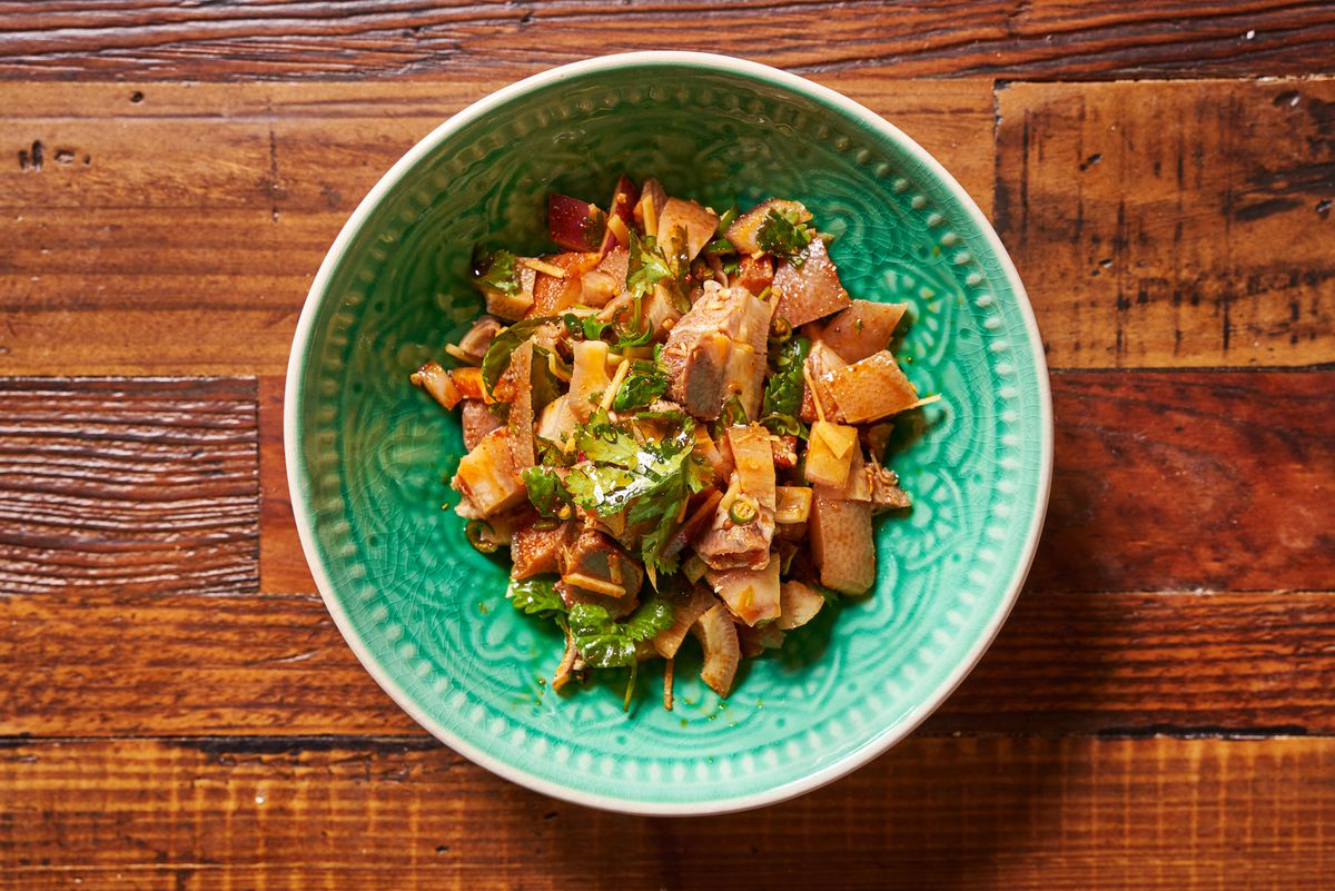 A pork salad placed in a green bowl kept on a wooden table