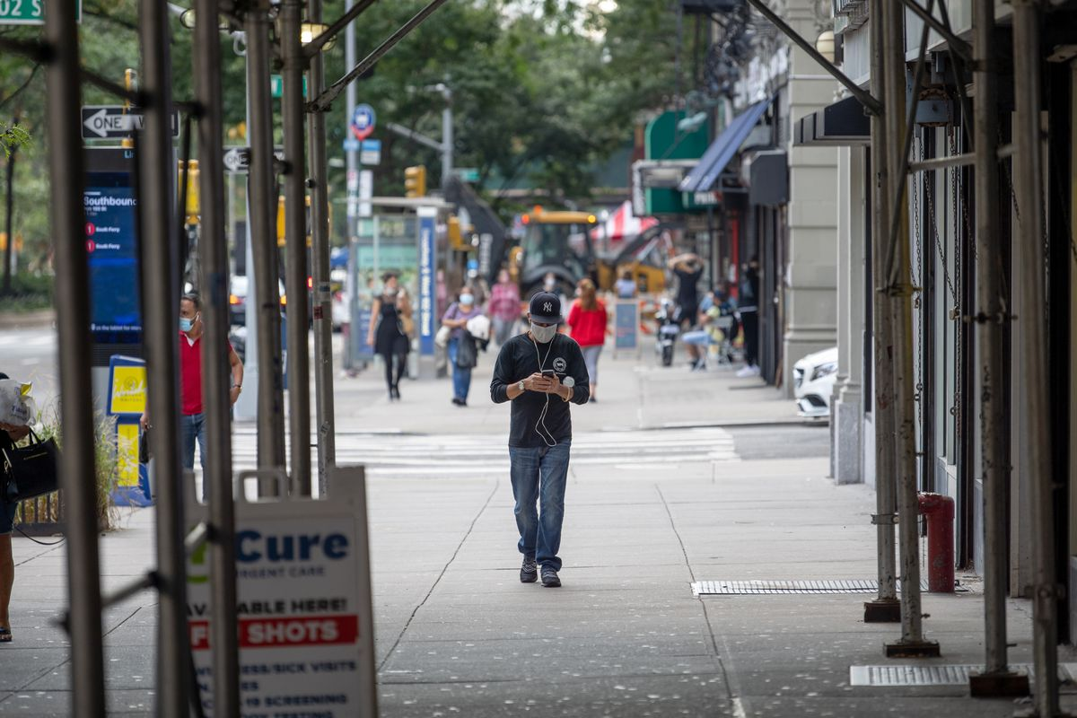A man wearing a mask walks down the street as the city continues Phase 4 of re-opening following restrictions imposed to slow the spread of coronavirus on September 28, 2020 in New York City.