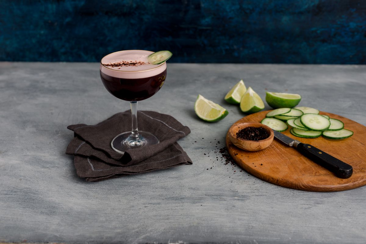 A dark purple cocktail sits on a gray table with cucumber, lime, and black aleppo pepper to the side