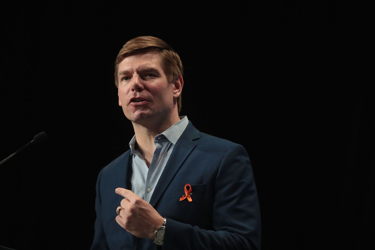 Eric Swalwell speaking while wearing a red ribbon pinned to his clothing.