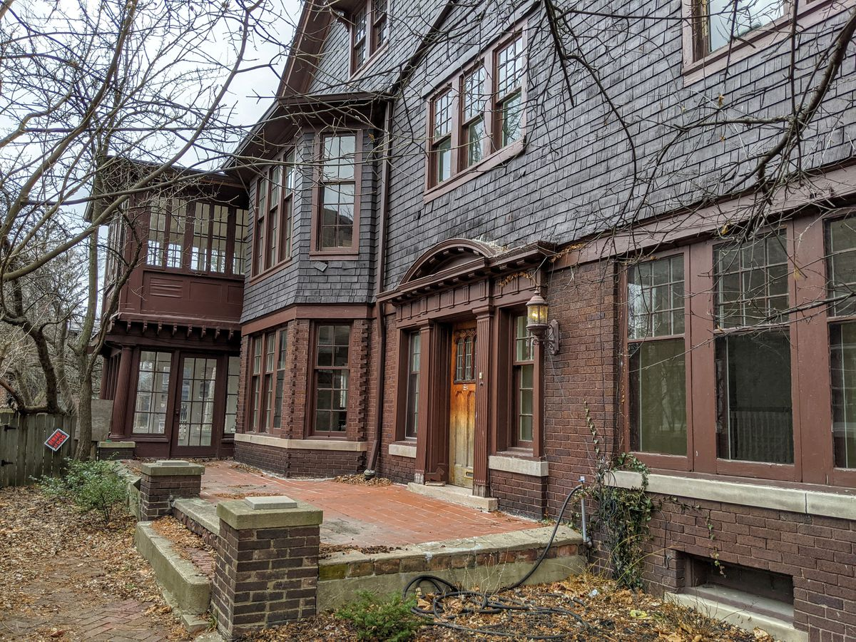 A view of the length of the home and a small, uncovered brick porch. There's a sun room for each floor.