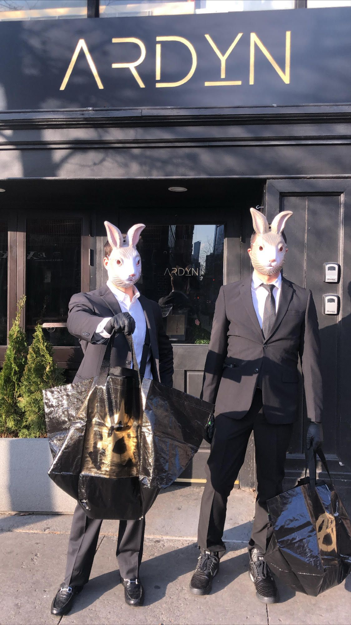 Two men standing outside of a restaurant dressed in black suits and bunny masks, holding bags of food for delivery