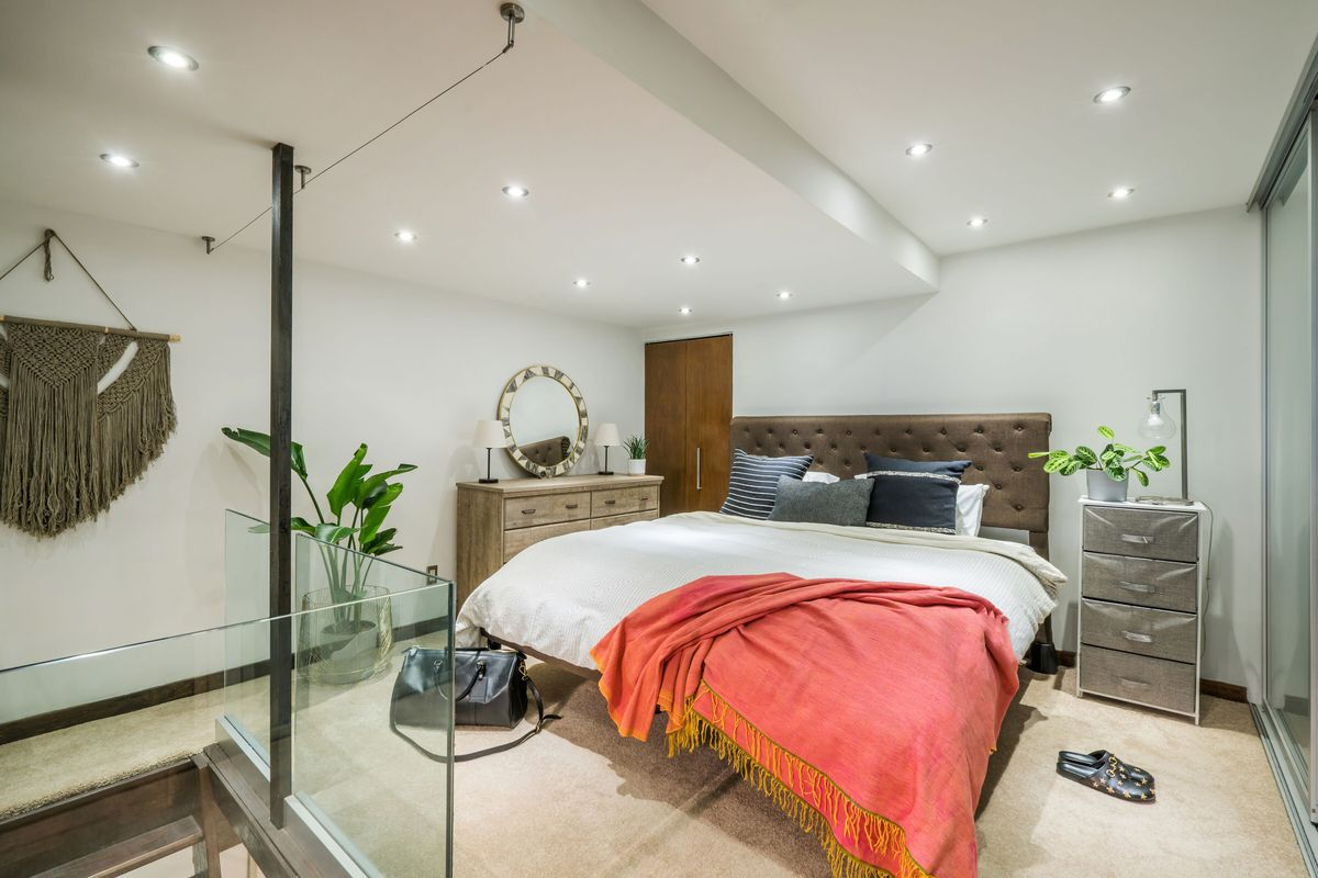 A lofted sleeping area with a large bed, white walls, and several planters.