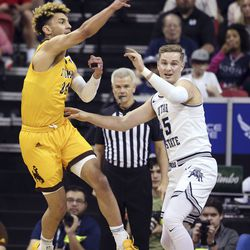 Wyoming's Hunter Maldonado (24) passes the ball as Utah State's Sam Merrill defends during the first half of an NCAA college basketball game in the Mountain West Conference men's tournament Friday, March 6, 2020, in Las Vegas.