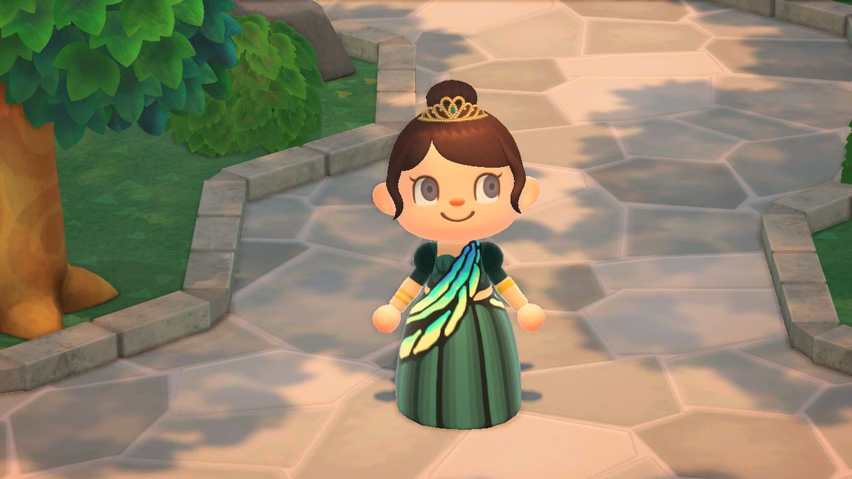 Animal Crossing: New Horizons - A character wearing a tiara and a tailored butterfly dress stands in the middle of a stone path under a tree.