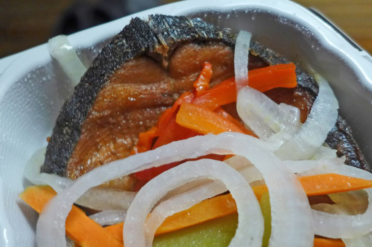 Slice of skin on brown fish strewn with pickled peppers and onions.