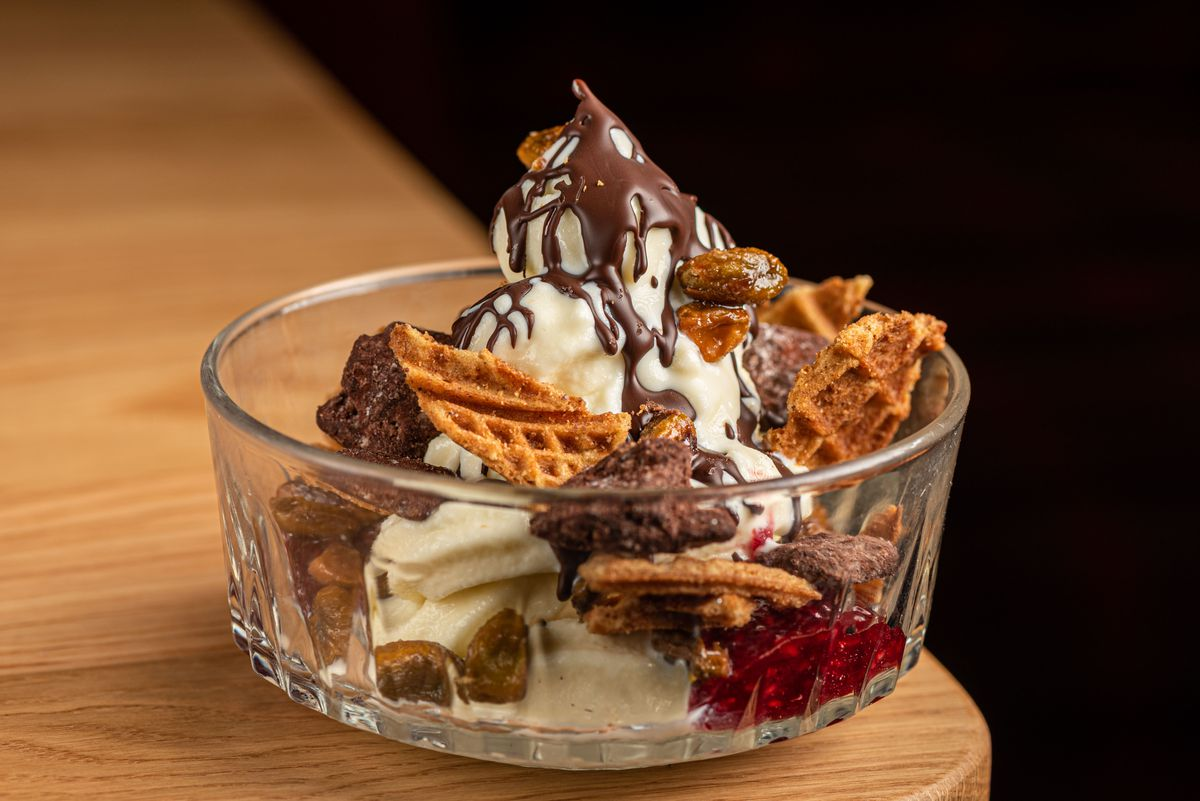 A glass bowl with soft serve ice cream and loaded with chocolate and lots of crispy bites.