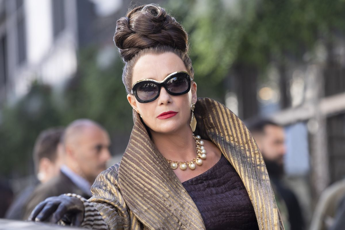 Emma Thompson as the Baroness. Her hair is up in an intricate hairstyle, she is wearing large sunglasses, gold earrings, a pearl necklace and a large gold coat.