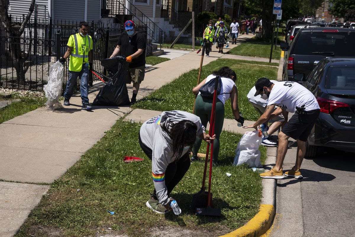 Volunteers pick up litter and clean up near West 23rd Street and South Cicero Avenue on Tuesday in Cicero after looting and violence spread through the town.