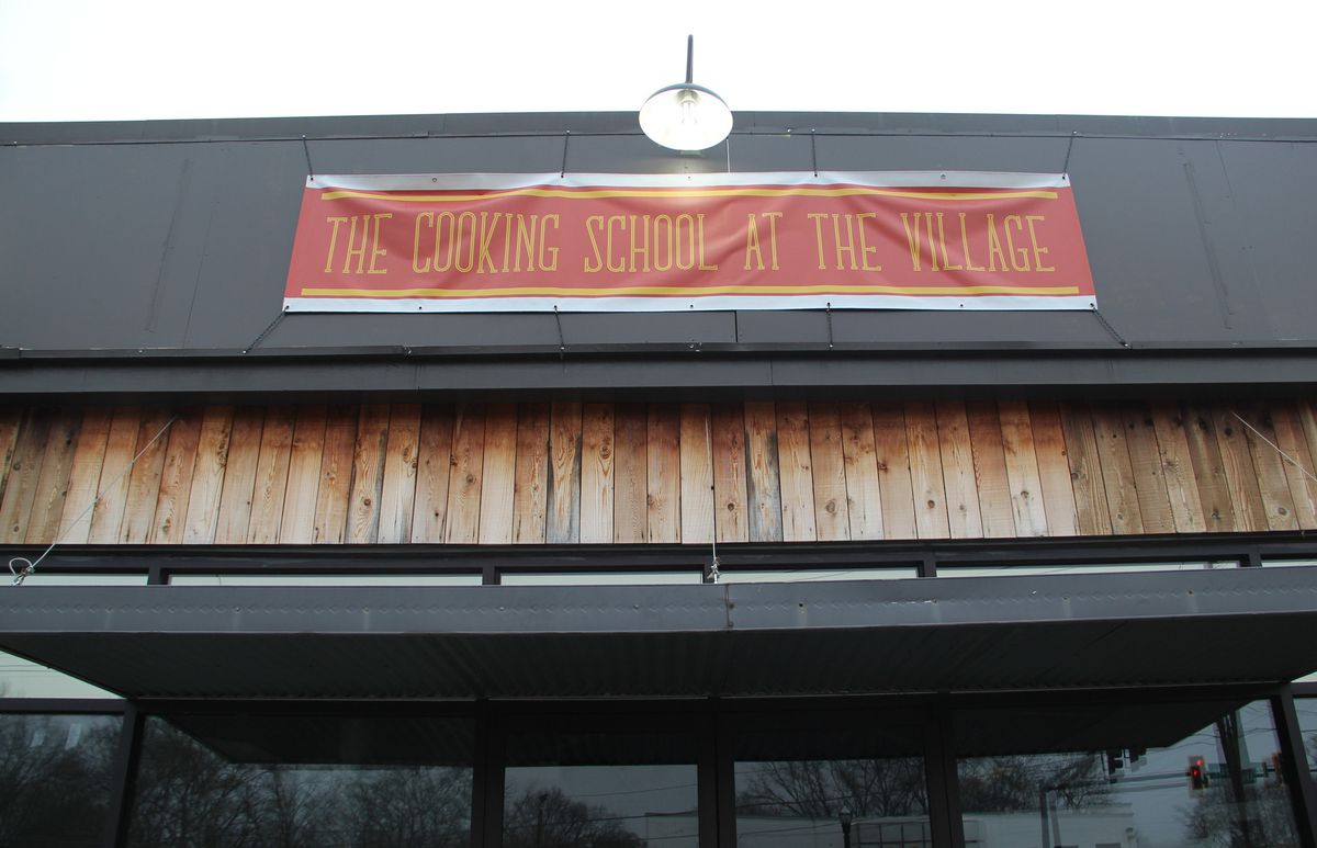 A banner that says The Cooking School at The Village over the doors of a building.