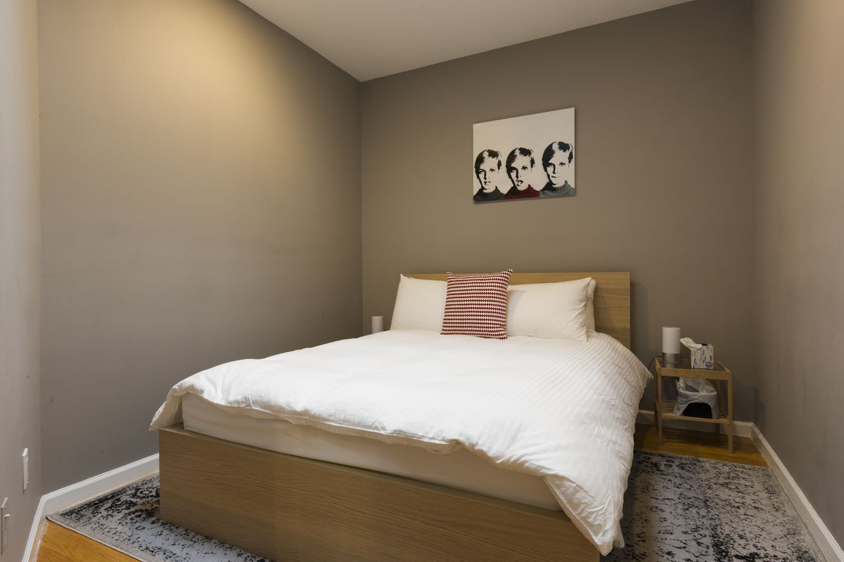 A bedroom with a medium-sized bed, grey walls, and hardwood floors.