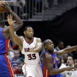 Atlanta Hawks' Willie Green (33) and Detroit Pistons' Rodney Stuckey, right, move around Pistons' Ben Wallace (6) during the second quarter of an NBA basketball game, Friday, April 6, 2012, in Atlanta.