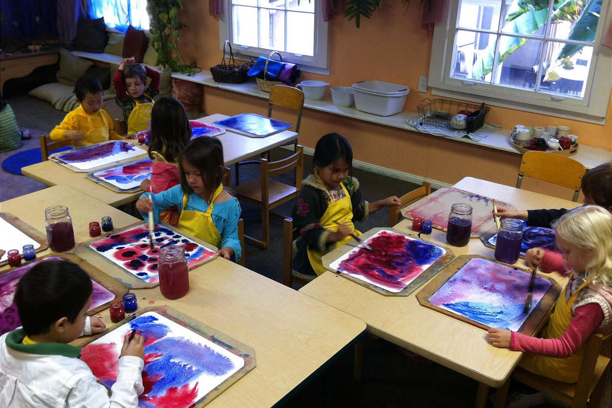Kindergarten children at Maple Village School in Long Beach California, a private Waldorf school,  doing a wet-on-wet watercolor experience in which they blend colors on the paper. The Waldorf emphasizes creative development over rote learning, especially