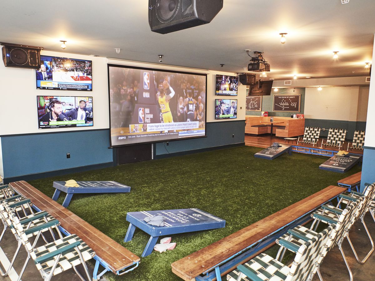 large projector screen on the wall surrounded by smaller tv's. Lawn chairs surround an astroturf covered area in front of the screen.