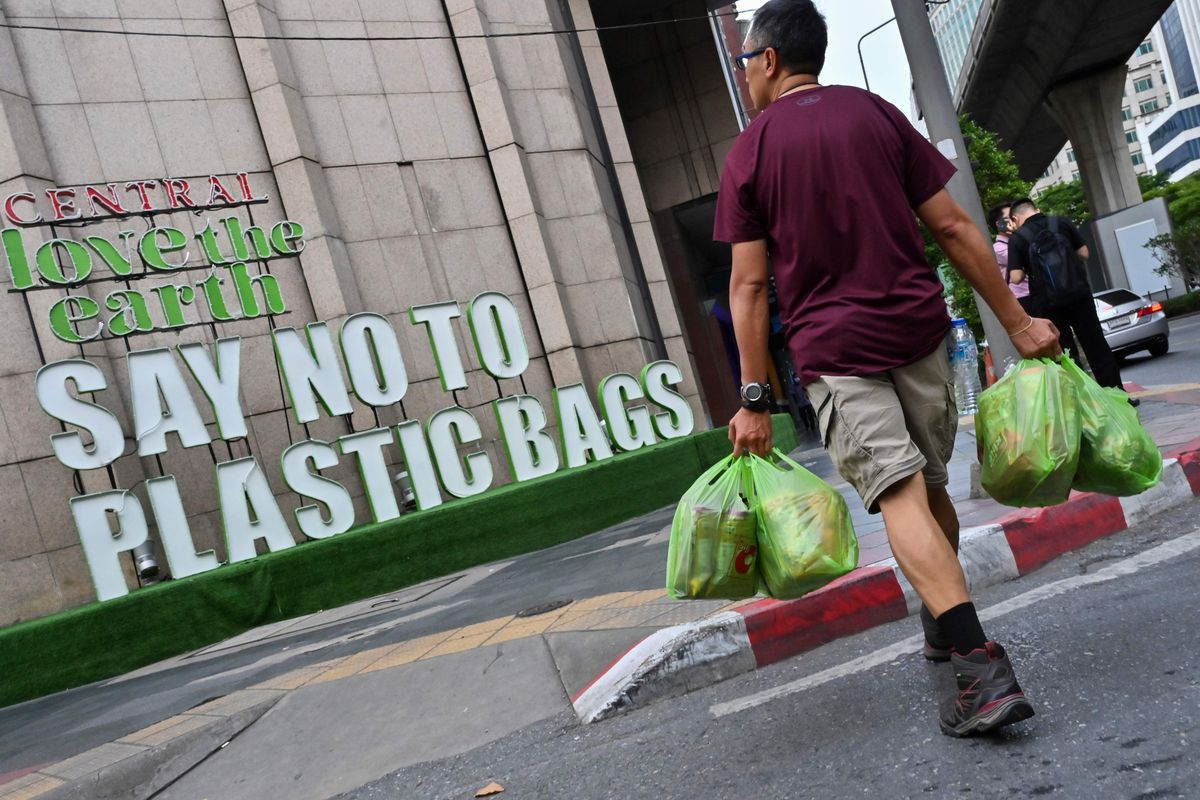 A man carrying goods in plastic bags walks past a sign promoting a plastic bag-free shopping experience, outside a store in Bangkok earlier this month.