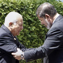 """Arab League Secretary-General Nabil Elaraby, left, greets Egyptian President Mohammed Morsi, as he leaves the Arab League headquarters in Cairo, Egypt, Wednesday, Sept. 5, 2012. Morsi says Syrian leader Bashar Assad must learn from """"recent history"""" and step down before it is too late."""