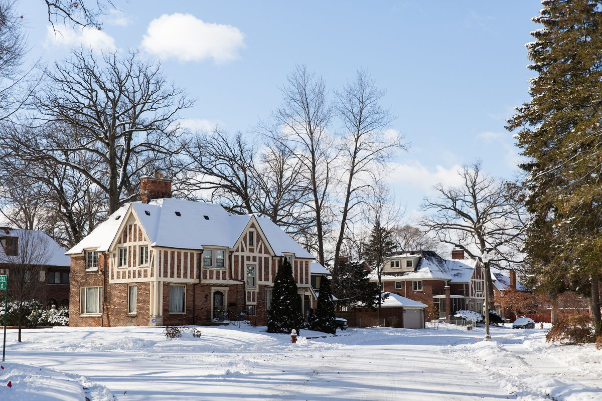 Two brown brick homes with roofs covered in snow. The road and sidewalks in the neighborhood are also covered in snow.