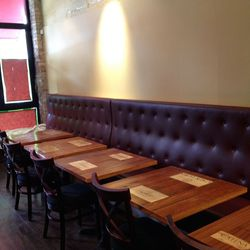 Tables, made of reclaimed wood from the ceiling, feature wine-crate name plates