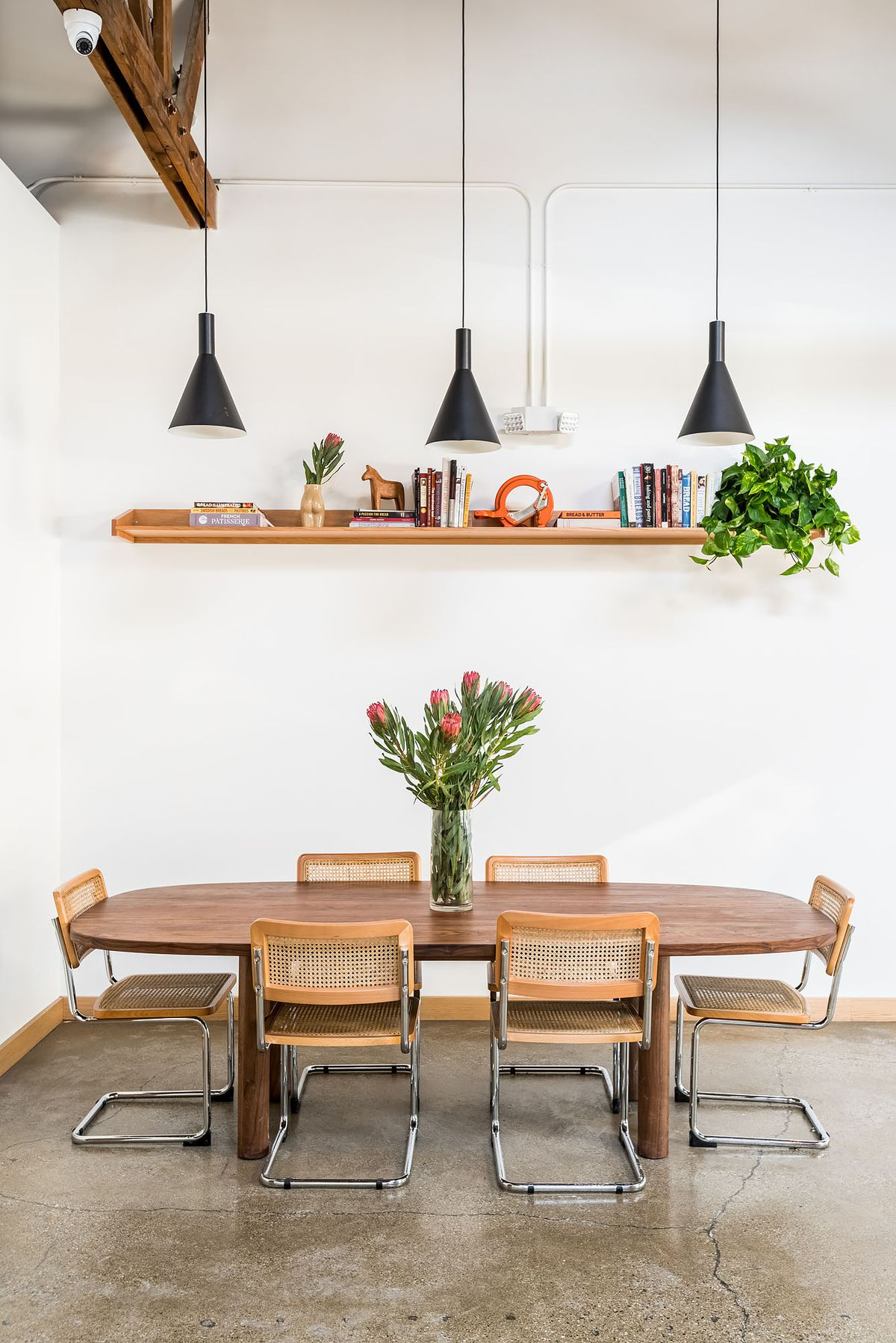 A communal wooden table in a white room restaurant.