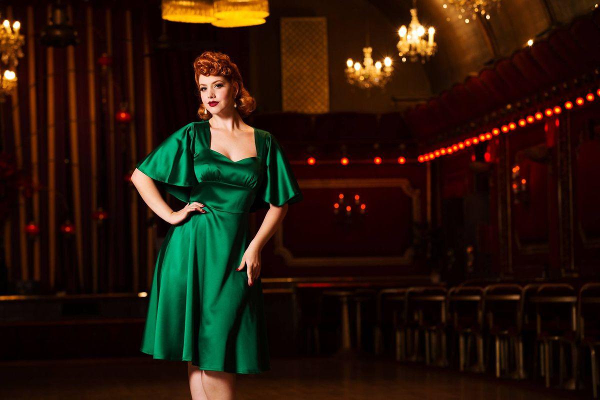 A model wearing a vintage green silk dress in a dimly lit bar