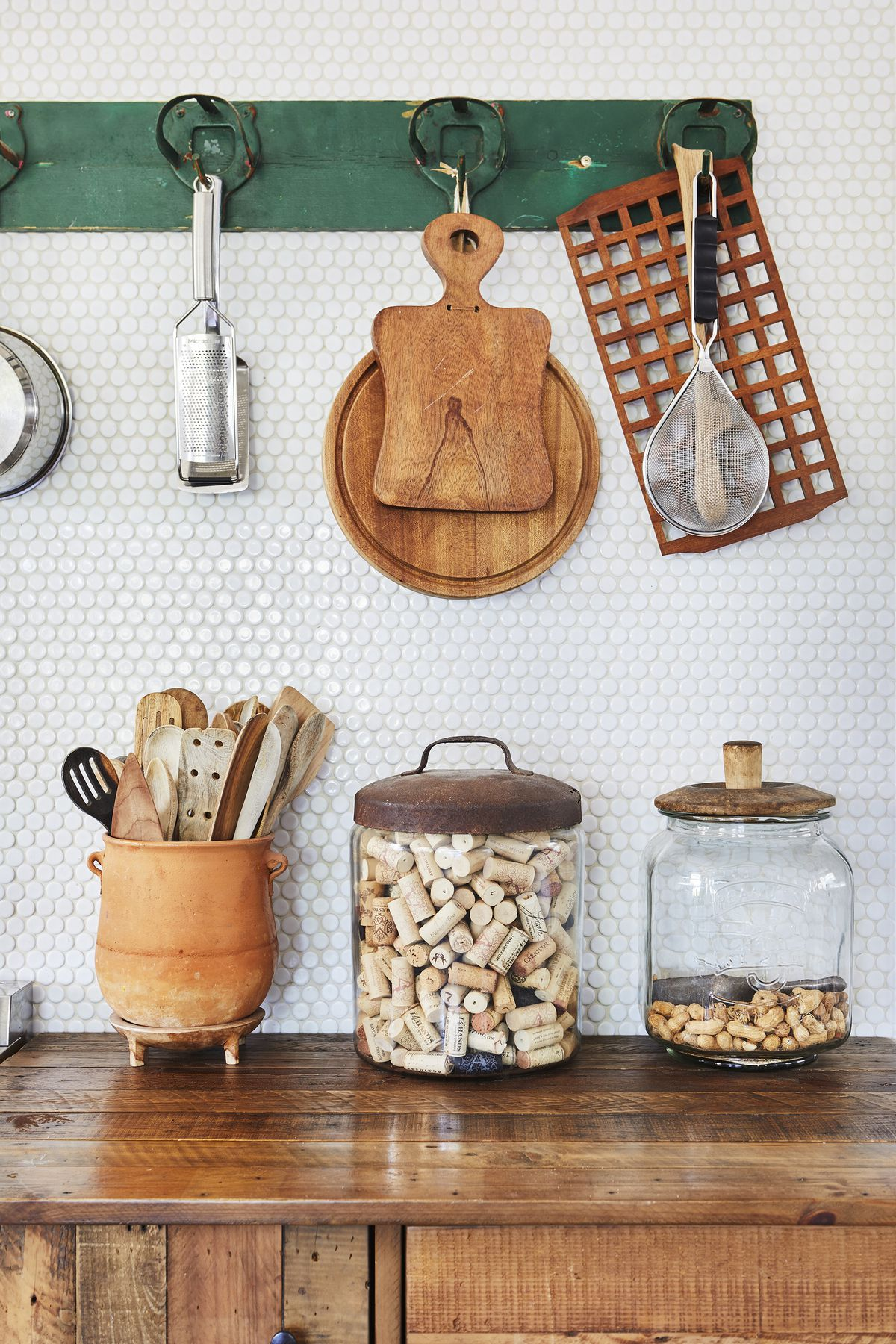 A green, metal rack hangs on a white-tiled wall in the kitchen. Below it, sit salvaged wood cabinets.