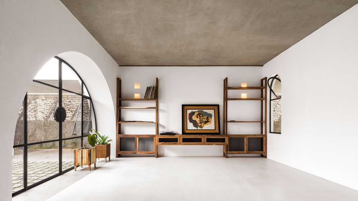Room with white-washed walls, arched doorway, concrete ceiling, and wooden bookshelves.