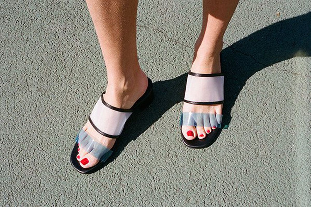 Model wearing mesh mule sandals with red polish on toes.